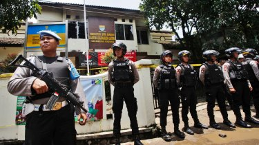 Police officers stand guard outside the municipal building in Bandung where police shot a suspected terrorist on Monday.