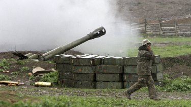 An Armenian covers his ears while a howitzer fires at an artillery position of the self-defence army of Nagorno-Karabakh near Martakert, Azerbaijan, on Sunday.