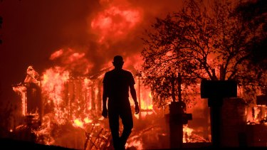Jim Stites watches part of his neighborhood burn in Fountaingrove, Califonia, on Monday.