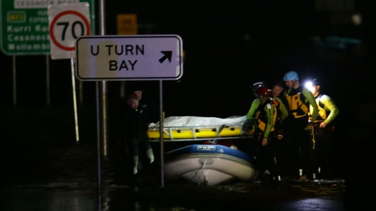 Police divers retrieve the body of an 86-year-old woman whose car was swept away.