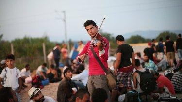 Syrian Rami Basisah plays for his fellow refugees at the Greece-Macedonia border in 2015.