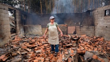 Inocencia Rodrigues, 64, walks among the debris of the burnt shed where she raised chickens and pigs in the village of Sao Joaninho, northern Portugal.