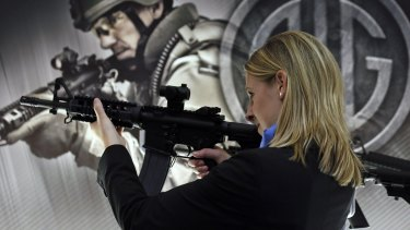 A woman tries out a SIGM400 rifle during the Defence & Security Equipment International arms fair in London in 2013.