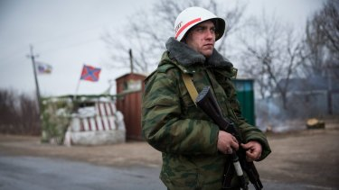 A pro-Russian separatist stands guard at a check point  on the road to Mariupol in March.