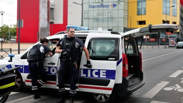Police officers respond to the hostage situation north of Paris in an unrelated incident in July.