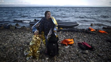A Syrian refugee woman and child arrive on a dinghy on the Greek island of Lesbos on Friday.