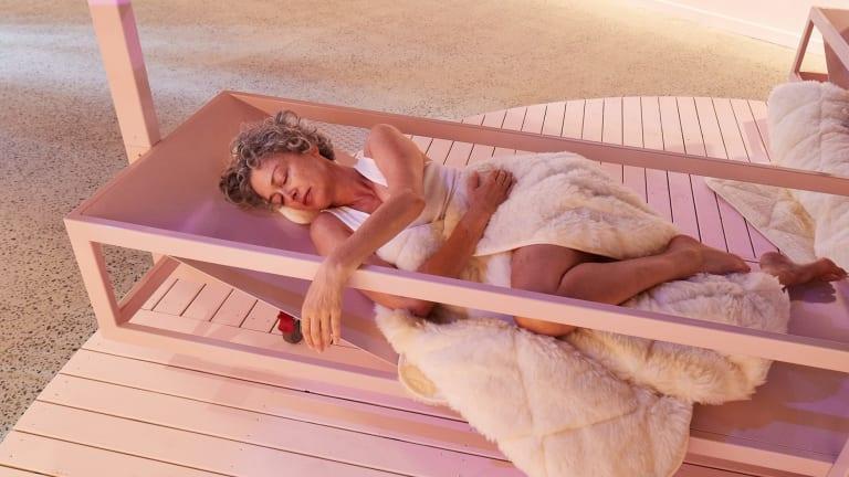 A sleeper is bathed in pink light in Matthew Bird's  speculative installation Dormitorium.
