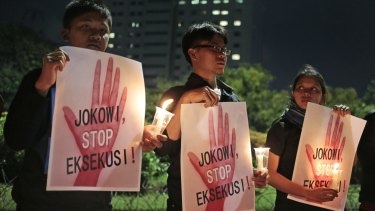 "Activists hold posters which read ""Jokowi, stop the executions!"" during a candle light vigil outside the presidential palace in Jakarta, on Thursday."