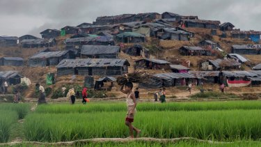A Rohingya Muslim boy carries firewood towards his shelter in Kutupalong refugee camp in Bangladesh on Monday.