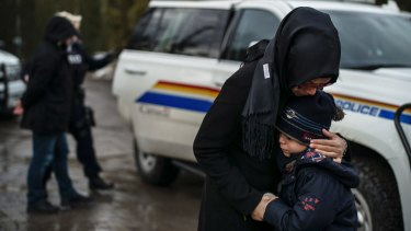 A woman comforts her son as his father is handcuffed by a Canadian police officer, having ignored the warning and crossed into Canada from Champlain, New York state.