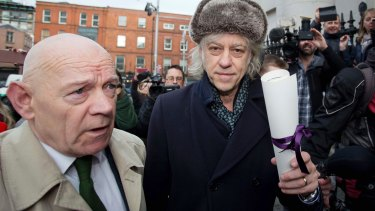 Irish rock singer Bob Geldof, right, holding his Freedom of the City of Dublin scroll with Councillor Mannix Flynn arrives at City Hall on Monday to hand it back