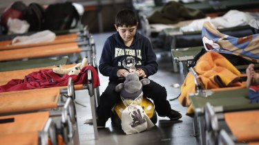 A boy plays as he waits with other refugees for registration at the temporary registration centre of the south German border town Passau.