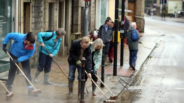 People continue the clean up effort, after the weekend's flooding, in Hebden Bridge, West Yorkshire.