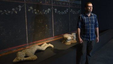 Curator Will Mather with some plaster casts of people killed in the eruption of Mount Vesuvius in 79AD.