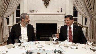 Turkey's then prime minister Ahmet Davutoglu, right, and Hamas leader Khalid Mishal speak during a dinner in Ankara in December 2015.