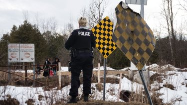 A Royal Canadian Mounted Police officer warns a family they will be arrested if they cross into Canada from Champlain, New York state, on February 23.