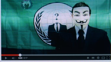 Video posted on youtube of an Anonymous member in a Guy Fawkes mask in front of the group's flag.