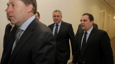 Treasurer Joe Hockey at the back of a big group accompanying Prime Minister Tony Abbott as he arrives for the party room meeting at Parliament House on Monday.