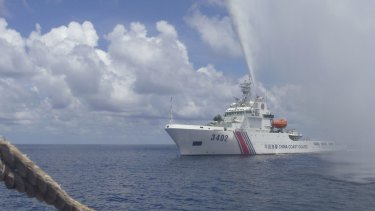 A Chinese Coast Guard boat sprays a water cannon at Filipino fishermen near Scarborough Shoal in the South China Sea.