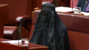 Pauline Hanson wears a burqa in Parliament House, prompting a stinging rebuke from George Brandis.