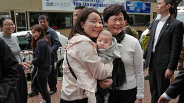 Hong Kong's chief executive elect Carrie Lam, centre right, poses with local residents in Hong Kong on Monday.