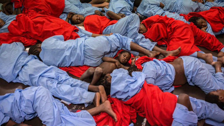Idris 3, from Mali, centre, sleeps next to his mother Aicha Keita, right, on the deck of the Golfo Azzurro vessel after being rescued from the Mediterranean sea off Libya in January.