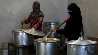 Syrian displaced women prepare food for refugees in the camp in Ain Issa, northern Syria.