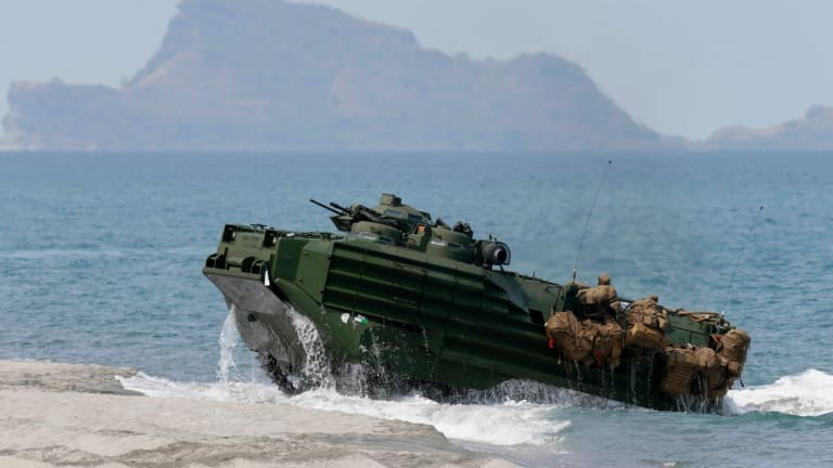A US Navy amphibious assault vehicle with Philippine and US troops on board storms the beach at a combined assault exercise opposite one of the disputed South China Sea islets.