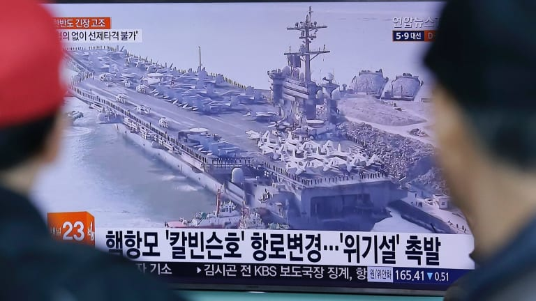 People in Seoul, South Korea, watch a TV news program showing the aircraft carrier USS Carl Vinson on Wednesday.