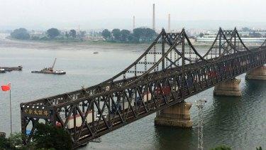 Tucks cross the friendship bridge connecting Dandong in China and Sinuiju in North Korea.