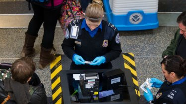 Transportation Security Administration (TSA) officers check passenger's identification at a security checkpoint at Ronald Reagan National Airport in Washington.