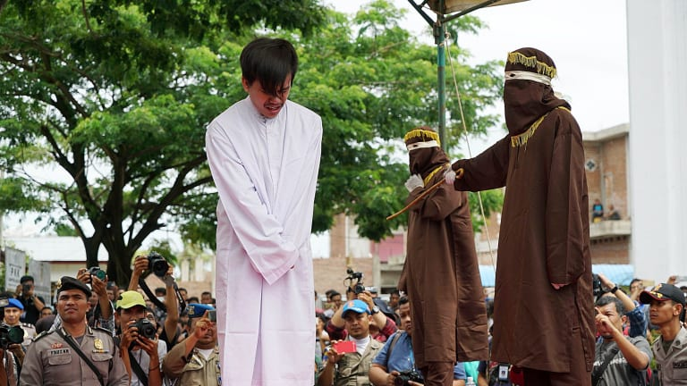 The masked men took turns to deliver the lashes  - 83 in the end - with a cane according to Aceh's sharia-inspired laws.
