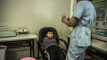 Temuulen Ganzorig, five, prepares to inhale medication through a nebuliser as part of his treatment for the flu at the Batchingun clinic in Ulaanbaatar.