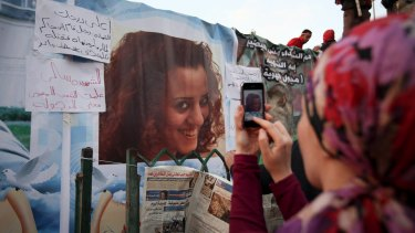 An anti-government protester takes a picture of a poster of Sally Zahran who was killed in during clashes in Tahrir Square in 2011.