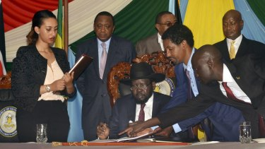 South Sudan President Salva Kiir, seated, signs a peace deal on Wednesday, watched by Kenya's President Uhuru Kenyatta, centre-left, Ethiopia's Prime Minister Hailemariam Desalegn, centre-right, and Uganda's President Yoweri Museveni, right.