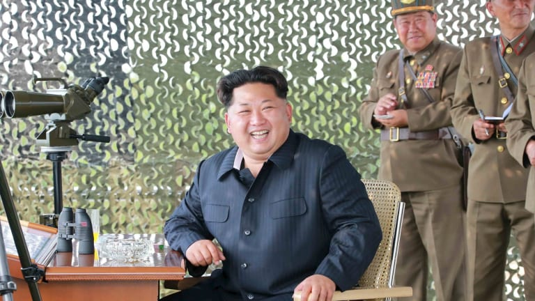 North Korean leader Kim Jong Un smiles as he watches a firing contest of anti-aircraft artillery personnel in this photo released by North Korea's news agency.