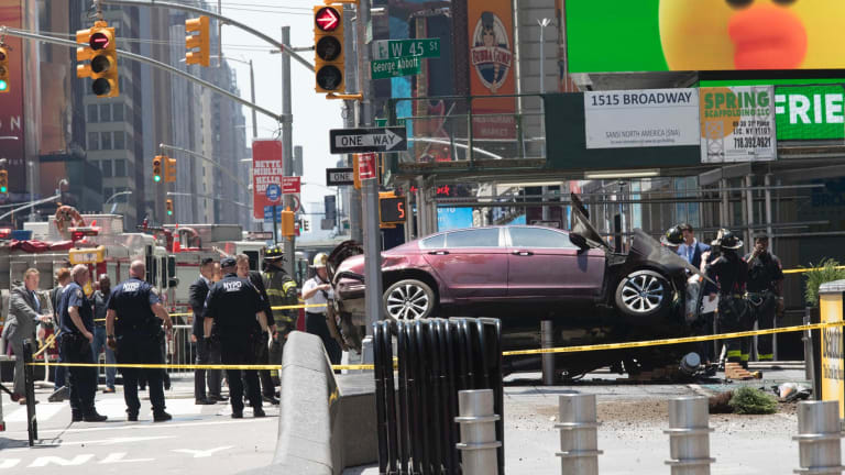 A car rests on a security barrier in New York's Times Square after driving through a crowd of pedestrians.