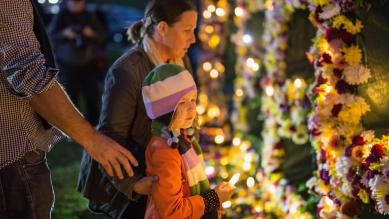 """A young girl is guided to place a candle on a flower wall that reads """"#keephopealive"""" as part of an Amnesty international vigil for the Bali nine duo, Andrew Chan and Myuran Sukumaran."""