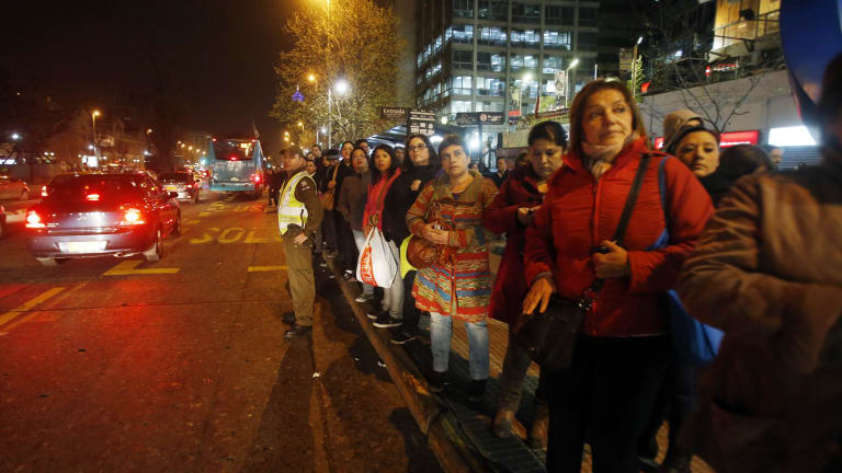 A police officer stands in the street to flag down buses to take people home after a powerful earthquake hit Chile's northern coast.