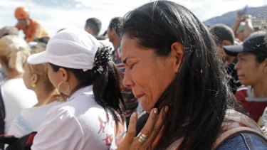 A Venezuelan woman cries as she crosses the Simon Bolivar bridge from Venezuela to Colombia to buy food on Sunday during a temporary opening of the border.