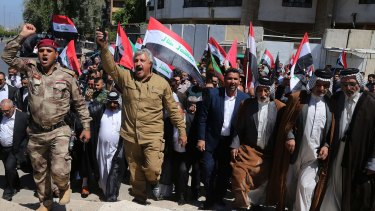 Iraqi Shiites wave the national flag as they celebrate victory over IS in the Iraqi city of Tikrit.