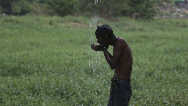 A man drinks water dripping from an overhead leaking pipe line in Hyderabad, India, on Monday.