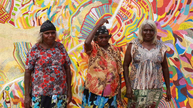 Artists Ngamaru Bidu, left, Kumpaya Girgirba and Nola Ngalangka Taylor standing in front of Yarrkalpa (Hunting Ground) 2013 at Martumili Art Studio, Parnngurr.