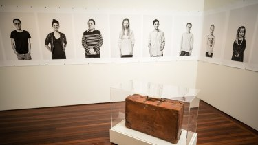 A suitcase and a series of portraits by Linda Wachtel feature in The Gift, an exhibition about migration at the Museum of Australian Democracy at Old Parliament House.