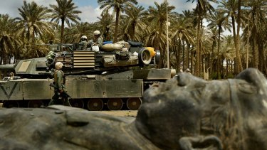 A US tank unit passes one of the many fallen statues of former Iraq dictator Saddam Hussein in Baghdad in 2003.