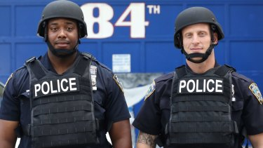 Jamal Skinner, left, and Evan Aronowitz model ballistic body armour ahead of NYPD plans to distribute 20,000 helmets and 6,000 vests to patrol officers before the end of the year.