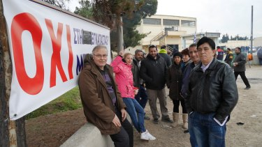 """Protesters next to a sign with the Greek word for """"No"""" outside a refugee camp near Thessaloniki."""