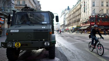 A cyclist rides past an armoured vehicle on Boulevard Anspach, Brussels, on Monday.