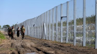 Hungarian soldiers walk along the border fence near the town of Morahalom, Hungary, on Monday.
