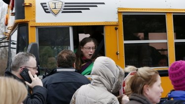 A school bus driver yells to a parent that their child is safe after a bus accident at Amy Beverland Elementary School left several students injured and the school principal dead on school grounds on Tuesday.